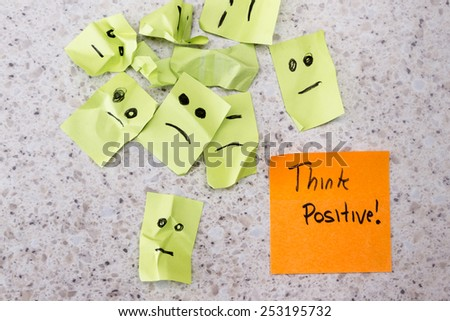 concept for a positive attitude with small crumbled up sad faces and a note with the phrase think positive - stock photo