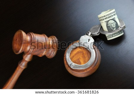 Concept For Corruption, Bankruptcy, Bail, Crime, Bribing, Fraud, Auction Bidding. Judges or Auctioneer Gavel, Soundboard And Bundle Of Dollar Cash On The Rough Black Wooden Textured Table Background. - stock photo