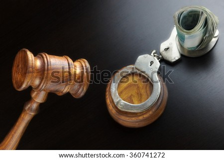 Concept For Corruption, Bankruptcy, Bail, Crime, Bribing, Fraud. Judges Gavel, Handcuffs   And Russian Cash On The Rough Black Wooden Textured Table Background.