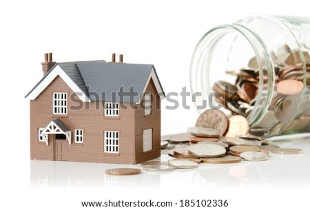 Concept for cost of living or housing a model house with coins  - stock photo