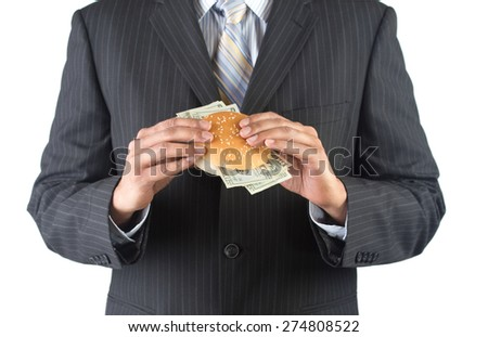 Concept for greed.  Concept for greedy corporate executives. Man in black suit and tie is eating a burger stuffed with money. Shot against a white background.  - stock photo