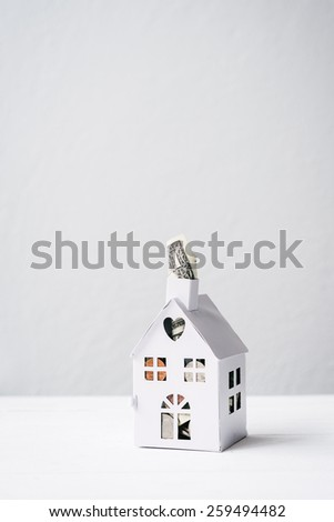 concept for saving for a house, mini house with $1 poking out - stock photo