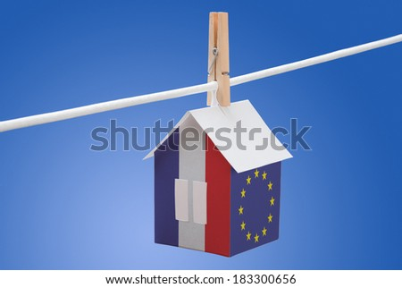 concept - France and EU flag painted on a paper house hanging on a rope - stock photo