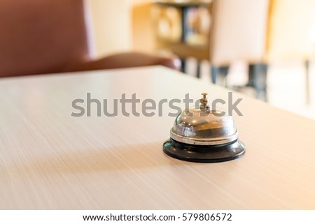 Concept hotel : old silver call bell on the wooden table, Hotel service bell on a table.
