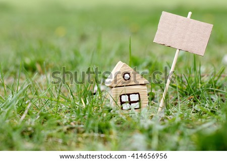 Concept house on nature with a sign for ads/selling ecological house in a nice area - stock photo