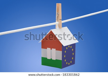 concept - Hungary, Hungarian and EU flag painted on a paper house hanging on a rope - stock photo