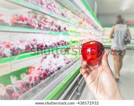 Concept,Husband hand hold and choosing apple at fruits store in the supermarket background. - stock photo
