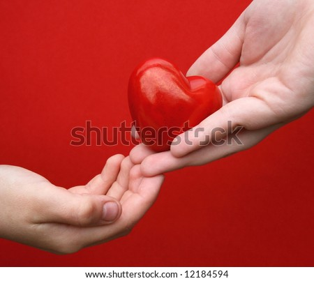"Concept/ Idea: ""I give you my heart"" .One hand give a heart in another hand in front of red background - stock photo"