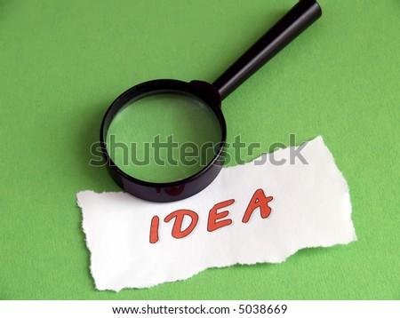 Concept 'idea': magnifier on green - stock photo
