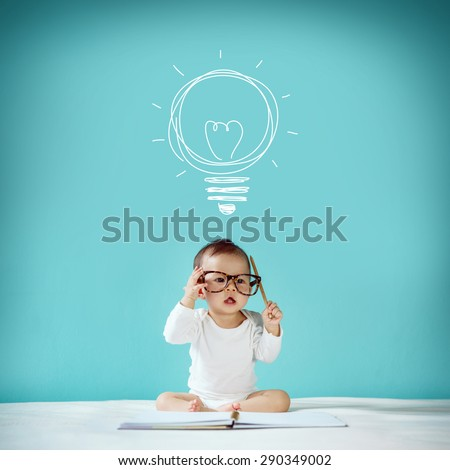 Concept, idea of happy little baby with bulb at blackboard, new family and love concept, studio shot - stock photo
