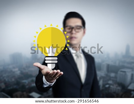 Concept, idea of young businessman with bulb in hand, new business in the city collection, studio shot - stock photo