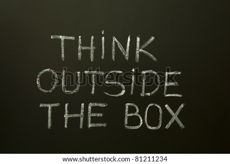 Concept image about unconventional or different thinking. 'Think outside the box' handwritten with white chalk on a blackboard. - stock photo