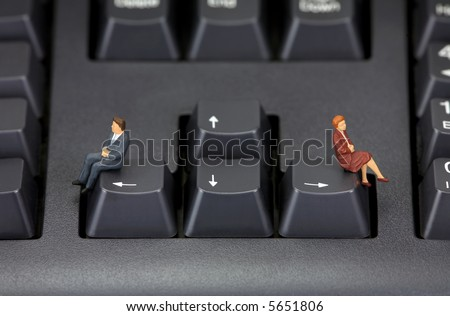 Concept image depicting a divorce or a relationship break-up. Two miniature figures are sitting on a computer keyboard in opposing directions. - stock photo