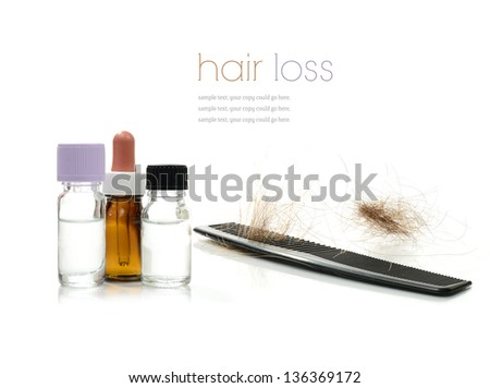 Concept image depicting alternative treatments for hair loss with medication bottles and comb against a white background. Copy space. - stock photo