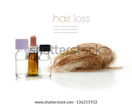Concept image depicting alternative treatments for hair loss with medication bottles and hair piece against a white background. Copy space. - stock photo