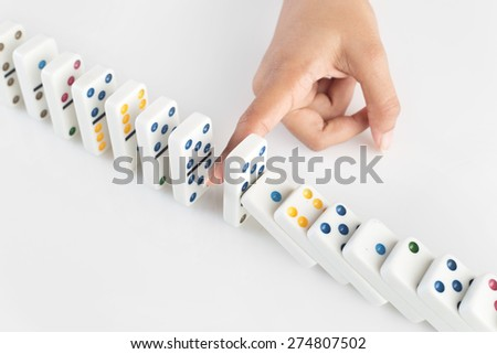 Concept image for business strategy and solution to crisis. Concept for  solution for  crisis situation, stopping a chain reaction of failures. Human finger stopping the domino effect. S - stock photo