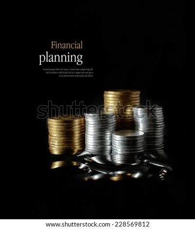 Concept image for financial planning. Creatively lit, stacked generic gold and silver coins representing client investment or savings. Copy space. - stock photo