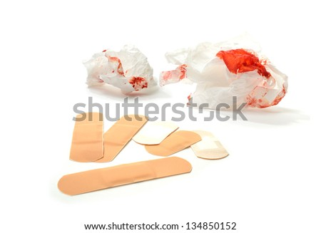 Concept image for first aid. NOT REAL BLOOD - Food coloring! - red stained tissues and plasters against a white background. Copy space. - stock photo
