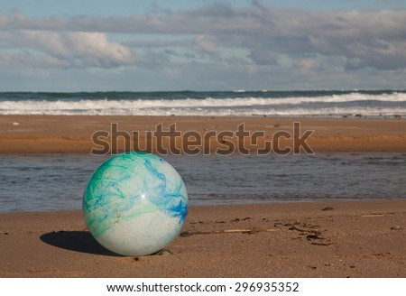 concept image for global environmental issue using inflatable rubber ball with earth like markings against an ocean beach background traditional landscape format  - stock photo