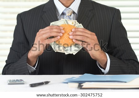 Concept image for greedy corporate business people. CEO is eating a burger stuffed with currency. He is at his desk in his office, wearing a black suit and tie.  - stock photo