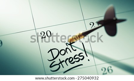 Concept image of a Calendar with a golden dart stick. The words Don't Stress written on a white notebook to remind you an important appointment. - stock photo