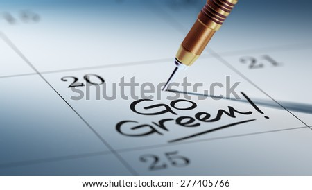 Concept image of a Calendar with a golden dart stick. The words Go Green written on a white notebook to remind you an important appointment. - stock photo