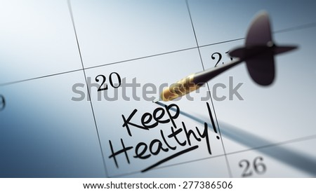 Concept image of a Calendar with a golden dart stick. The words Keep Healthy written on a white notebook to remind you an important appointment.