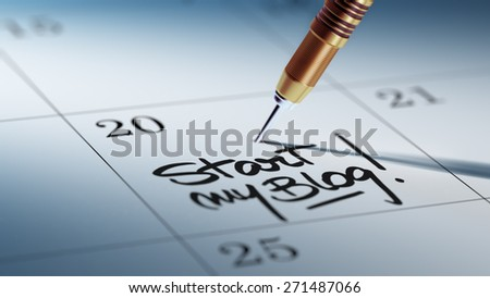Concept image of a Calendar with a golden dart stick. The words Start my Blog written on a white notebook to remind you an important appointment. - stock photo