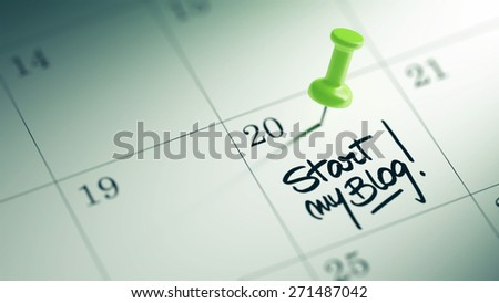Concept image of a Calendar with a green push pin. Closeup shot of a thumbtack attached. The words Start my Blog written on a white notebook to remind you an important appointment. - stock photo