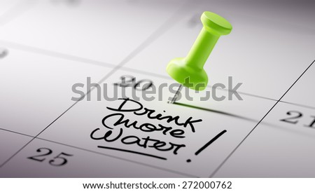 Concept image of a Calendar with a green push pin. Closeup shot of a thumbtack attached. The words Drink more water written on a white notebook to remind you an important appointment. - stock photo