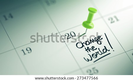 Concept image of a Calendar with a green push pin. Closeup shot of a thumbtack attached. The words Change the world written on a white notebook to remind you an important appointment. - stock photo
