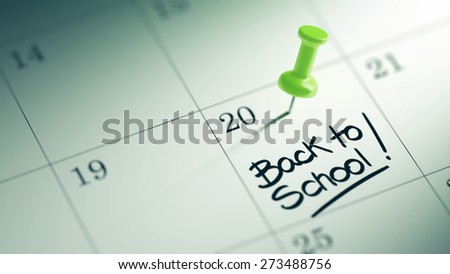 Concept image of a Calendar with a green push pin. Closeup shot of a thumbtack attached. The words Back to school written on a white notebook to remind you an important appointment. - stock photo