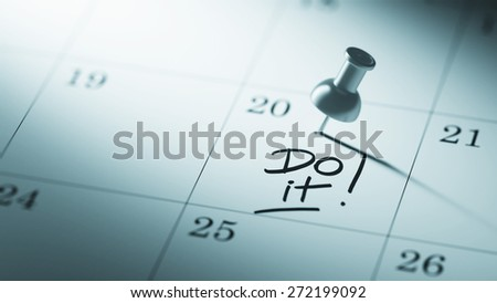 Concept image of a Calendar with a push pin. Closeup shot of a thumbtack attached. The words Do it written on a white notebook to remind you an important appointment. - stock photo