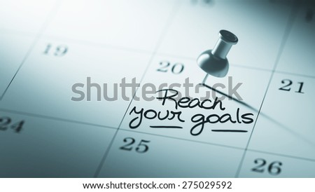 Concept image of a Calendar with a push pin. Closeup shot of a thumbtack attached. The words Reach your goals written on a white notebook to remind you an important appointment. - stock photo