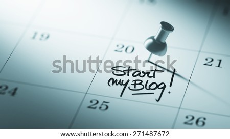 Concept image of a Calendar with a push pin. Closeup shot of a thumbtack attached. The words Start my Blog written on a white notebook to remind you an important appointment. - stock photo