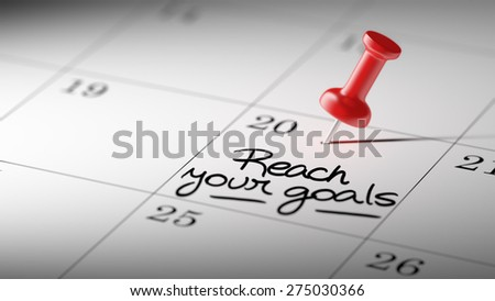 Concept image of a Calendar with a red push pin. Closeup shot of a thumbtack attached. The words Reach your goals written on a white notebook to remind you an important appointment. - stock photo