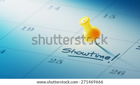 Concept image of a Calendar with a yellow push pin. Closeup shot of a thumbtack attached. The words Showtime written on a white notebook to remind you an important appointment. - stock photo