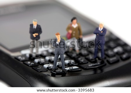 Concept image of a group of miniature businessmen and businesswomen standing on the keys of a cellphone. Focus is on the man in the center. - stock photo