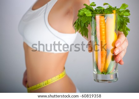 Concept image of a woman holding a glass of vegetables in front of her body - stock photo