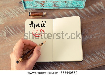 Concept image of April 22 Calendar Day with empty space for text as handwritten note with fountain pen on a notebook - stock photo
