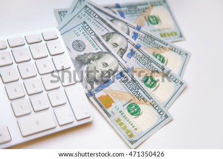 Concept image of finance and investment. 100 US dollars bank notes and money coins. with computer keyboard.