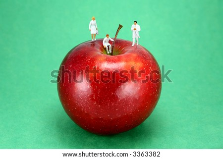 "Concept image of miniature doctors standing on an apple, representing the old saying ""An apple a day keeps the doctor away."" The apple is red and it's against a light green background."