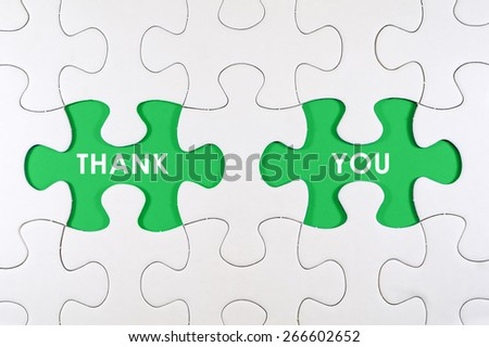 Concept image of missing puzzle pieces with THANK YOU words on green