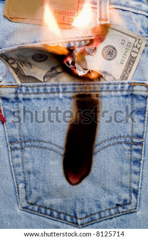 Concept image of money burning a hole in a jeans pocket - stock photo