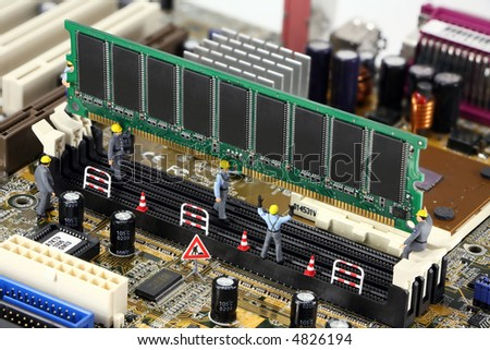 Concept images of miniature construction workers installing computer memory on a motherboard. - stock photo