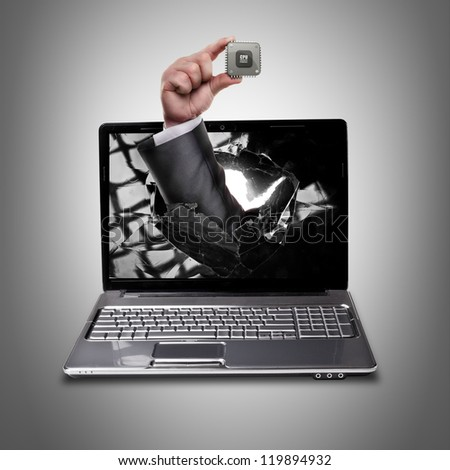 CONCEPT. laptop with broken screen and hand hand holds the processor CPU High resolution - stock photo