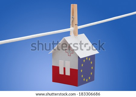 concept - Malta, Maltese and EU flag painted on a paper house hanging on a rope - stock photo