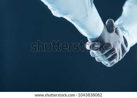 concept of a reliable partnership: a close-up of handshake of business partners on a black background.