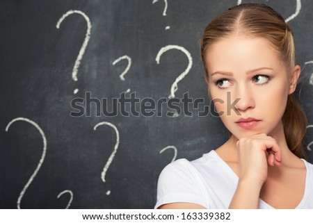 concept of a woman and a question mark drawn in chalk on the blackboard - stock photo
