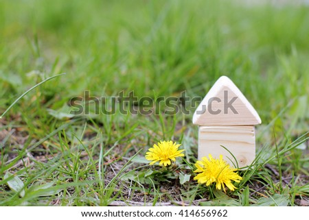concept of a wooden house on a plot with grass and flowers/house in ecological region - stock photo